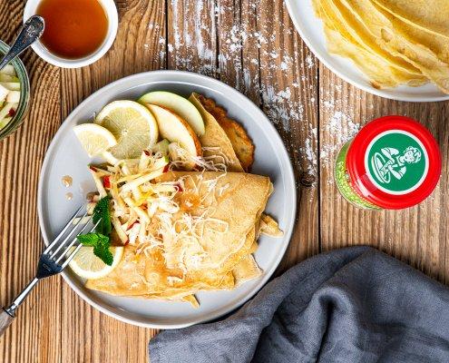 Teller mit Dinkelpfannkuchen mit Meerrettich, Minze, Apfel und Ahornsirup