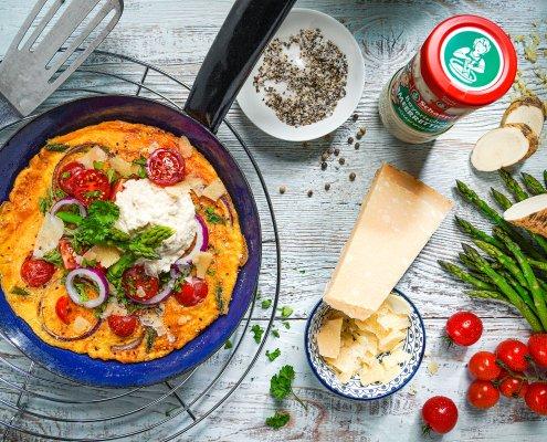 Pfanne mit Omelett mit grünem Spargel, Tomaten und Meerrettich